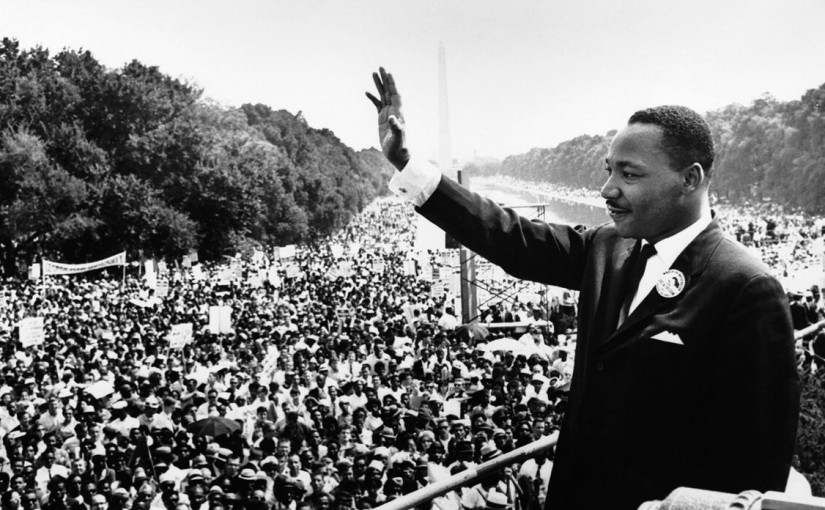 Martin Luther King raises his right hand in a wave, with thousands of people on the Washington Mall behind him