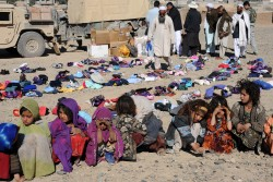 Afghan refugee girls wait at the end of a long line of 150 residents that live in the Farah City District V Refugee Camp to receive donated items sent from the United States and delivered to the camp by the Farah Provincial Reconstruction Team Civil Affairs Team, Jan. 9. The items, including shoes, winter coats and blankets, were sorted and distributed by Abdul Khaaleq Amini, director of the Department of Refugees and Repatriation office for Farah province, with the help of two Afghan national police officers and several refugee elders who also live in the camp.