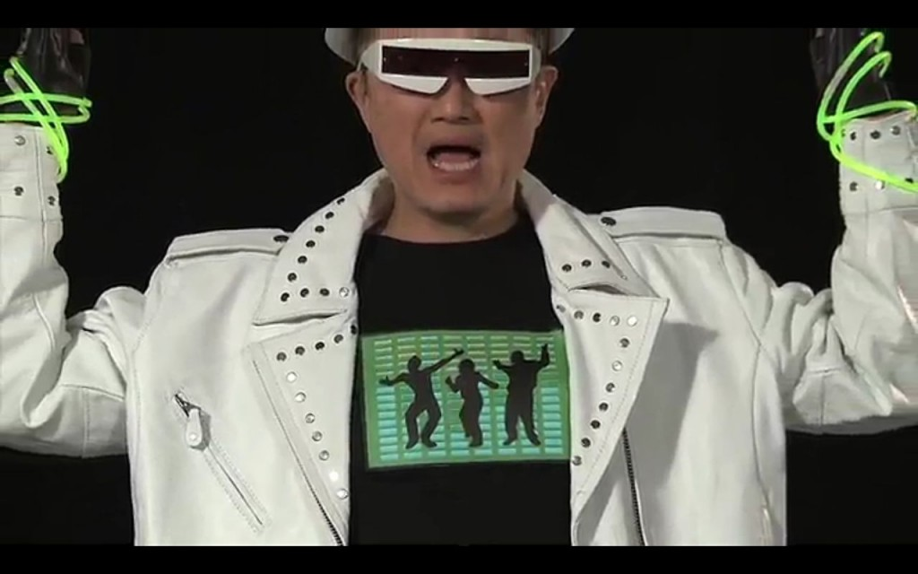A still from a video showing Jim Kim in a white leather jacket, dancing