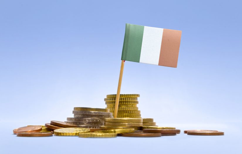 Flag of Ireland in a mixed stack of european coins and a blue background.(series)