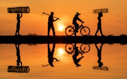 Four men on their way to work at sunrise. One is on a bicycle.